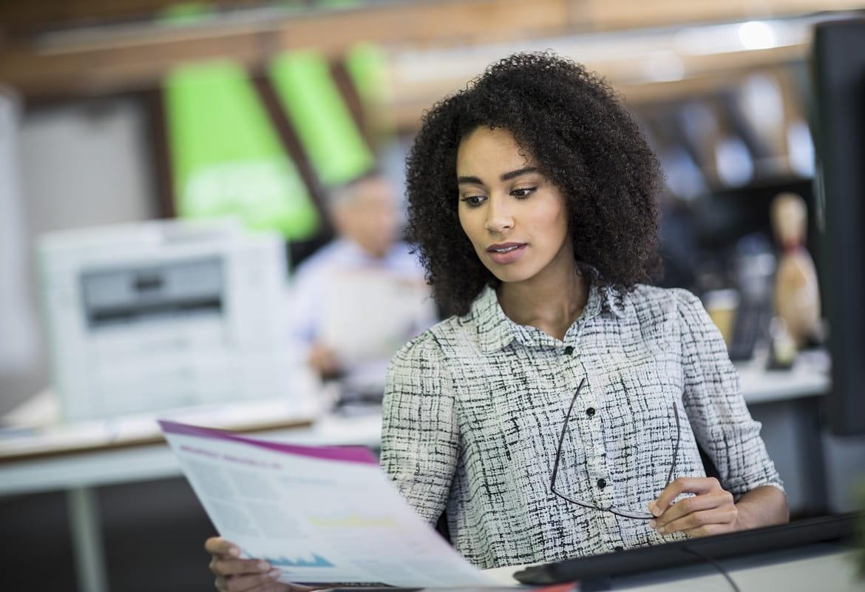 Impiegata in ufficio con foglio A3 a colori stampato con stampante inkjet professionale Brother