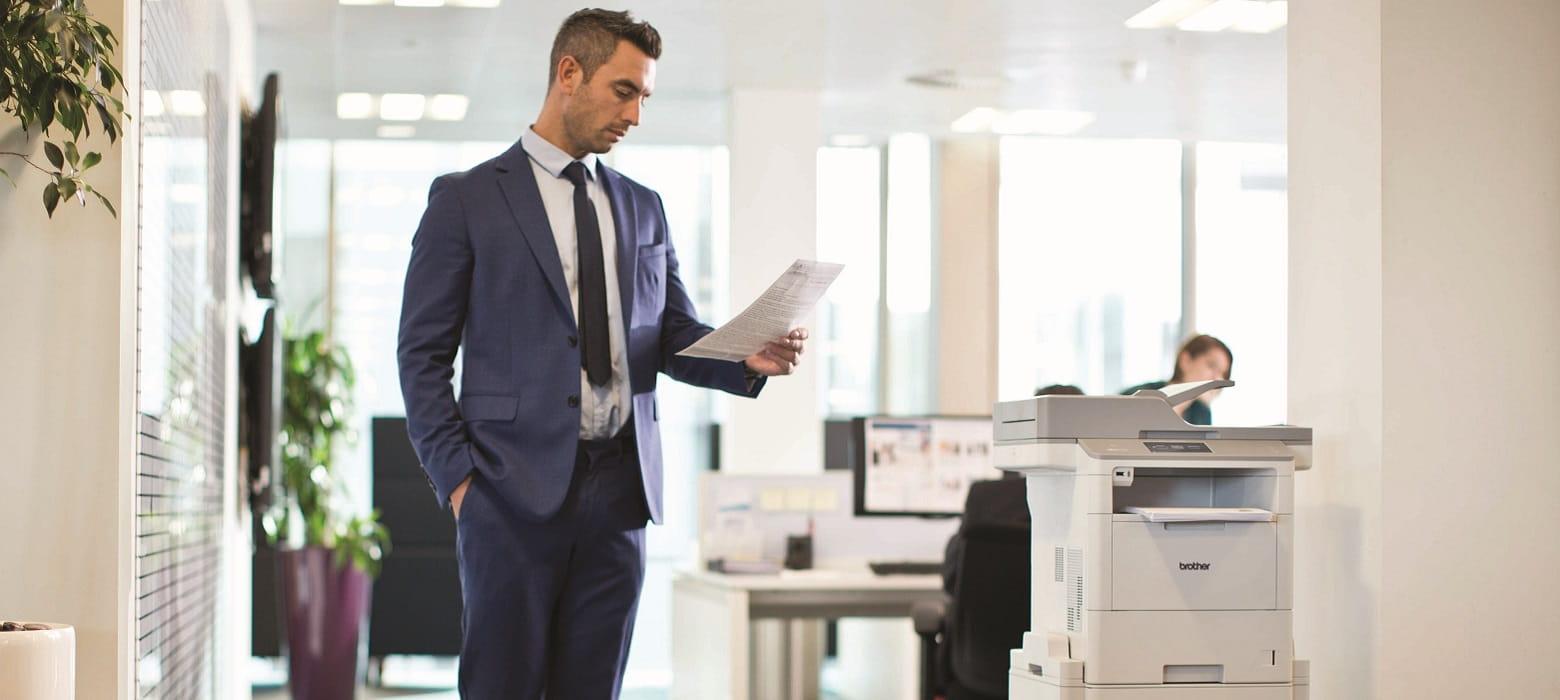Impiegato in ufficio guarda foglio stampato con stampante multifunzione laser Brother MFC-L6900DW