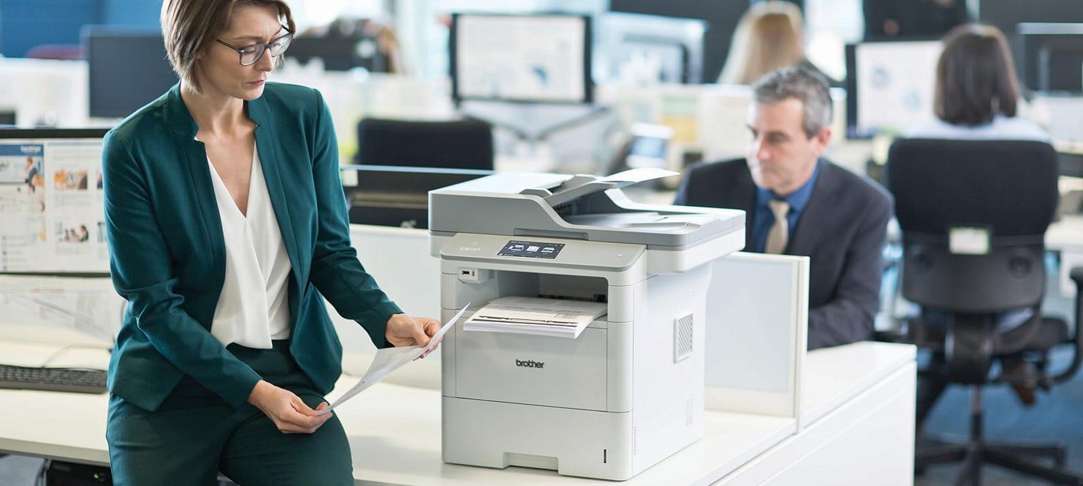 Impegiata seduta in ufficio su scrivania con multifunzione laser monocromatico Brother DCP-L6600DW