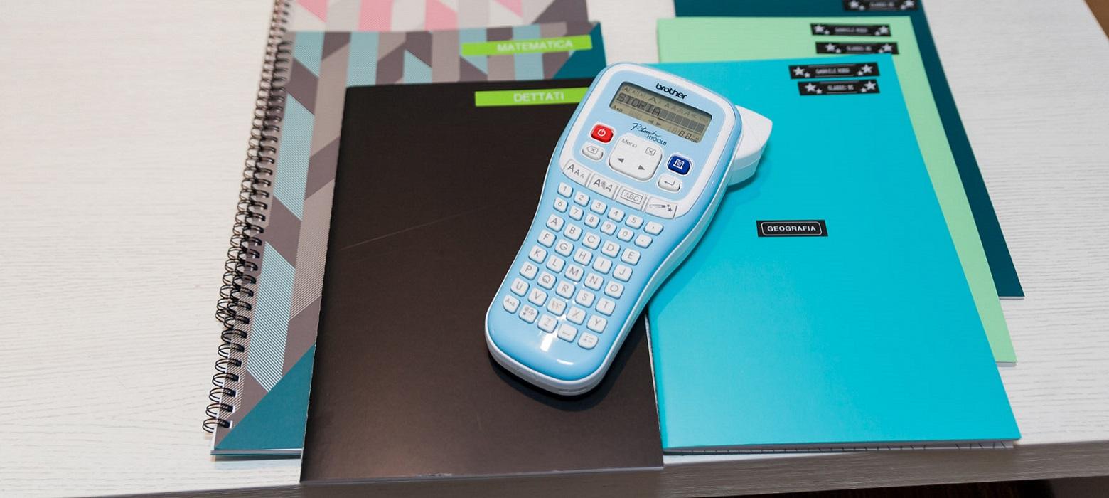 Etichettatrice Brother PT-H100LB su scrivania con quaderni etichettati