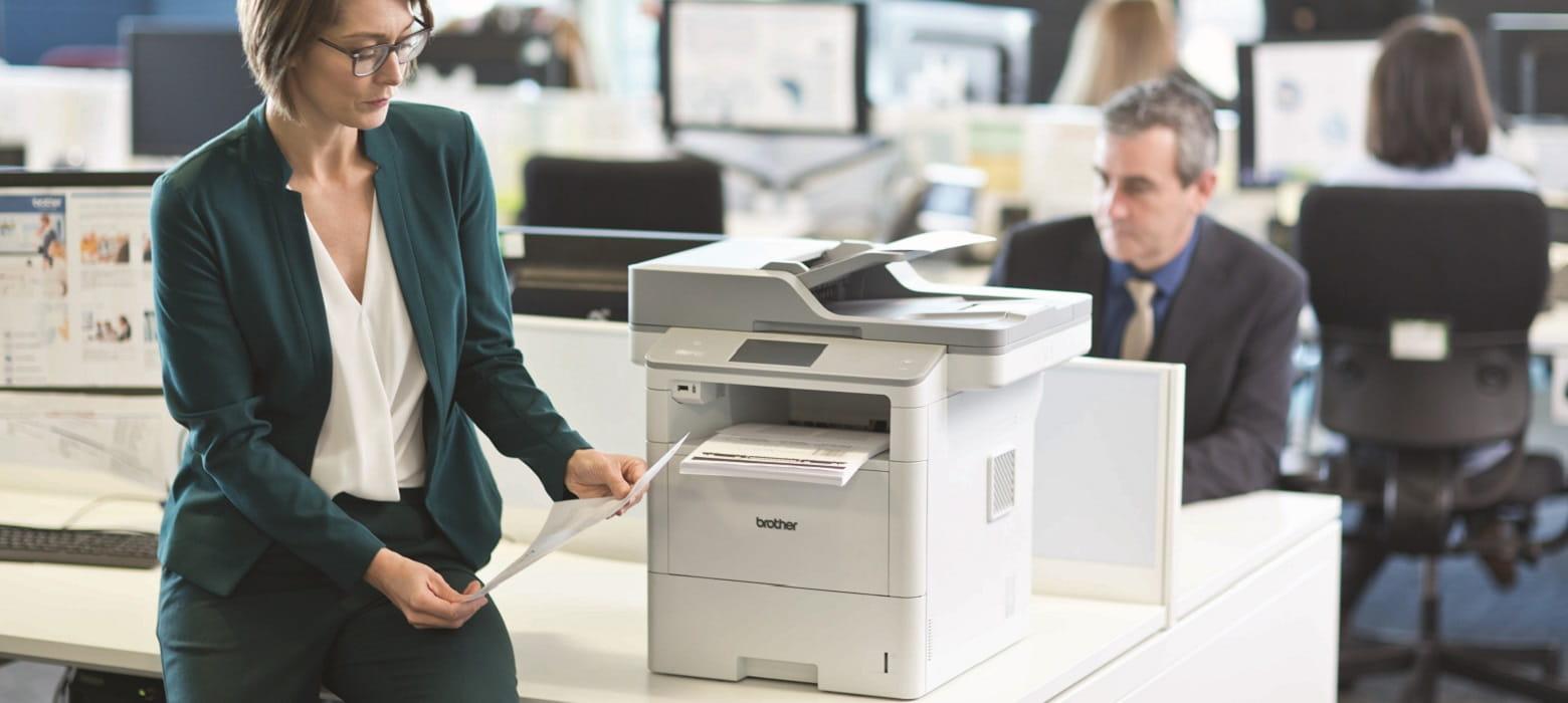 Impiegata in ufficio con fogli stampati da stampante multifunzione laser monocromatica Brother MFC-L6900DW