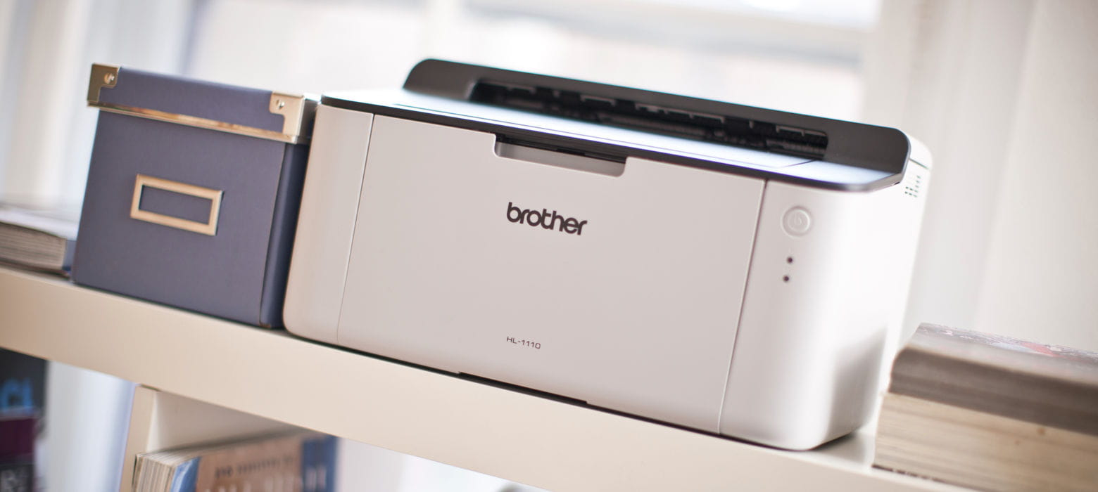 Stampante laser monocromatica compatta Brother HL-1110 poggiata comodamente su un armadio