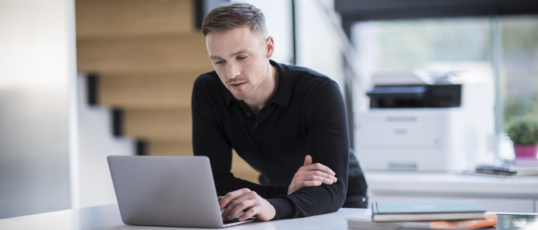 Ragazzo in ufficio scrive al PC con dietro una stampante multifunzione laser Brother