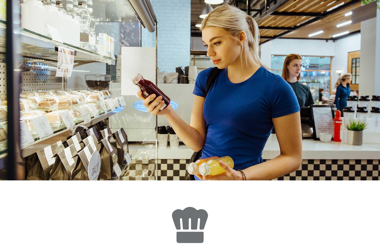 Donna con capelli biondi e maglietta blu legge etichetta di un succo di frutta