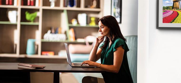 Donna alla scrivania con il laptop, libreria arredata sullo sfondo