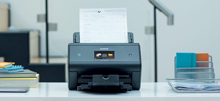 Scanner desktop Brother ADS-3600W sul tavolo con documenti in scansione