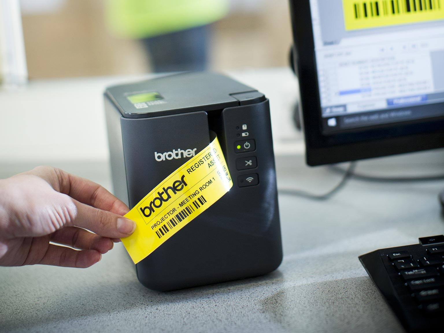 Brother P-touch P900W label printer with a yellow label being printed from a PC