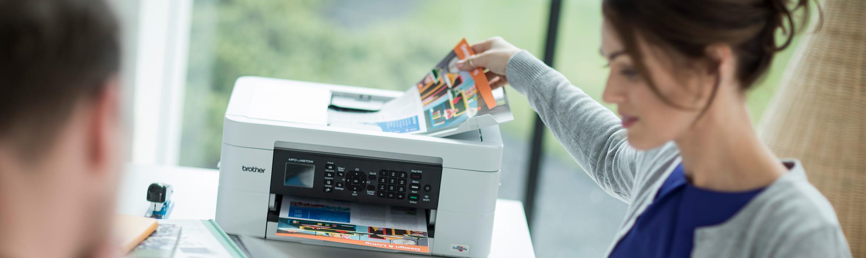 Donna che prende un foglio dalla stampante Brother
