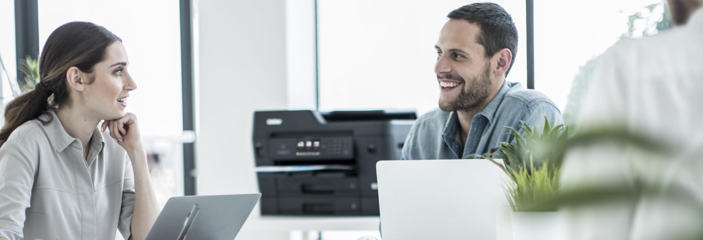 Impiegati che discutono in ufficio con una stampante multifunzione inkjet A3 Brother MFCJ6930DW sullo sfondo
