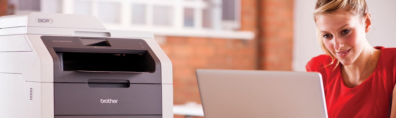 Impiegata al lavoro su laptop con stampante multifunzione Brother DCP