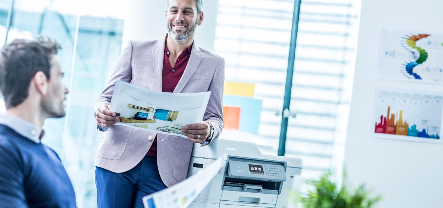 colleghi sorridenti in ufficio che stampano con stampante Brother MFC-J6935DW
