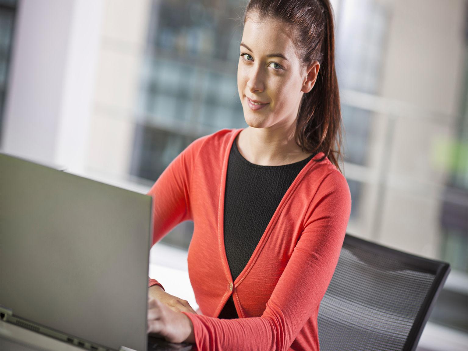 Impiegata in ufficio al lavoro su PC portatile