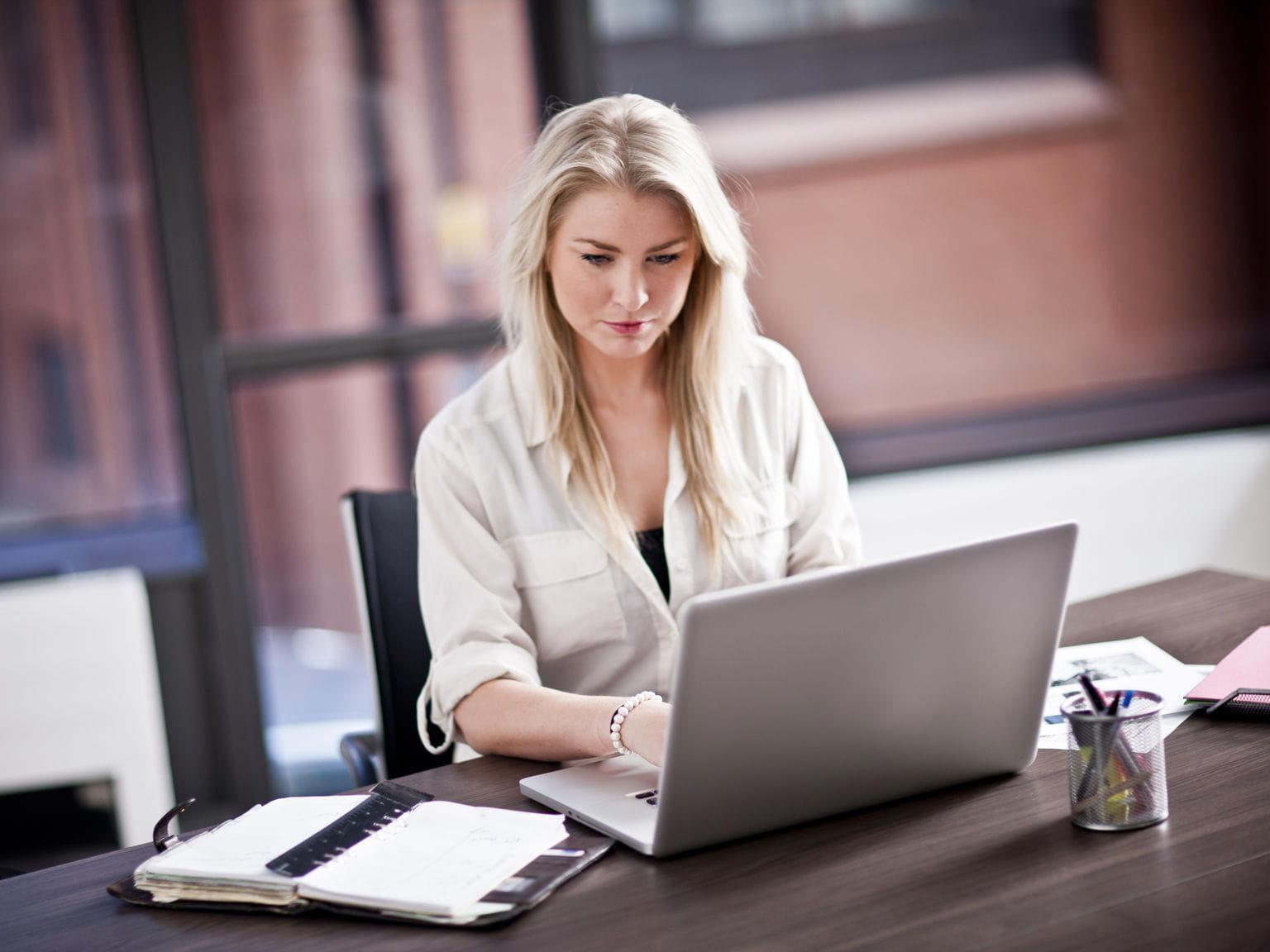impiegata in uffico con portatile durante orario lavoro