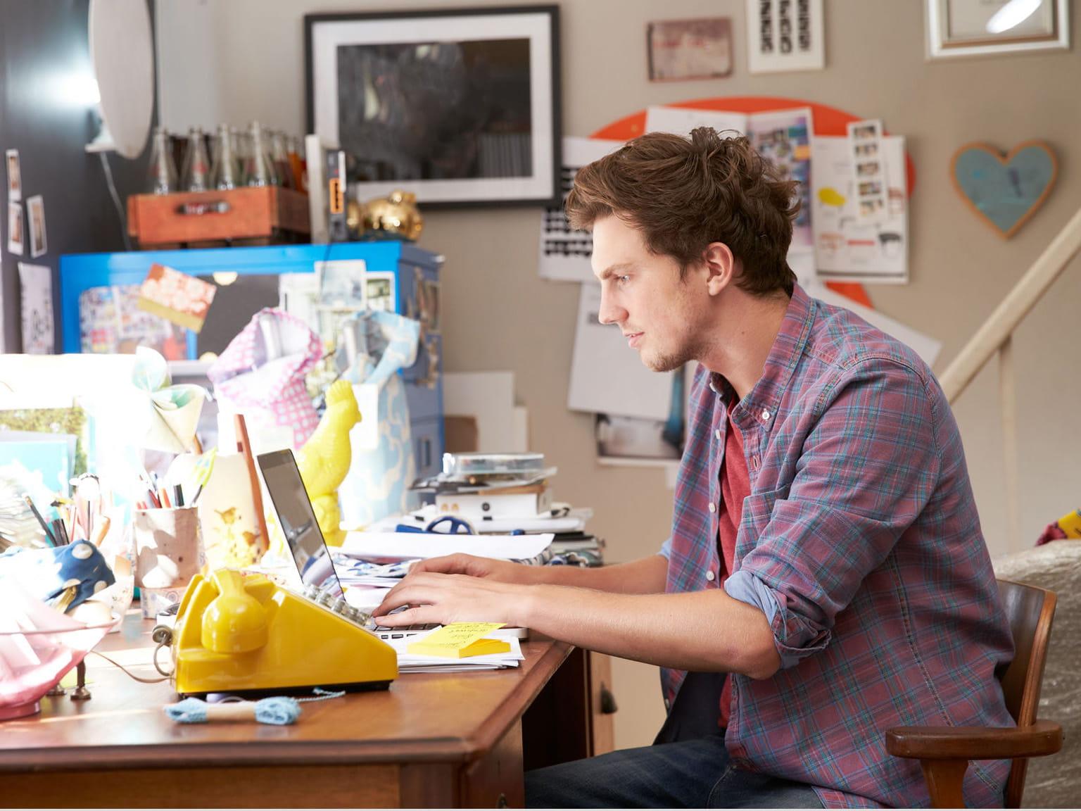 Ragazzo al lavoro nel suo uffico in casa