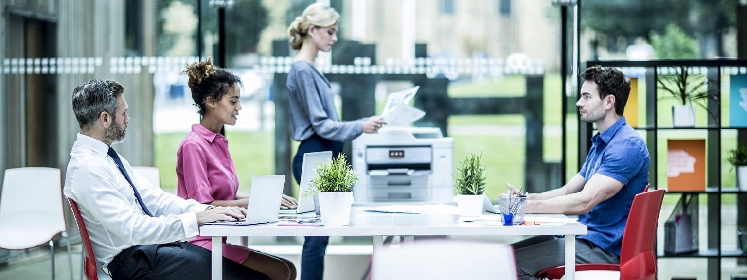 Riunione in ufficio open space con impiegata con foglio stampato da stampante multifunzione Brother MFCJ5930DW