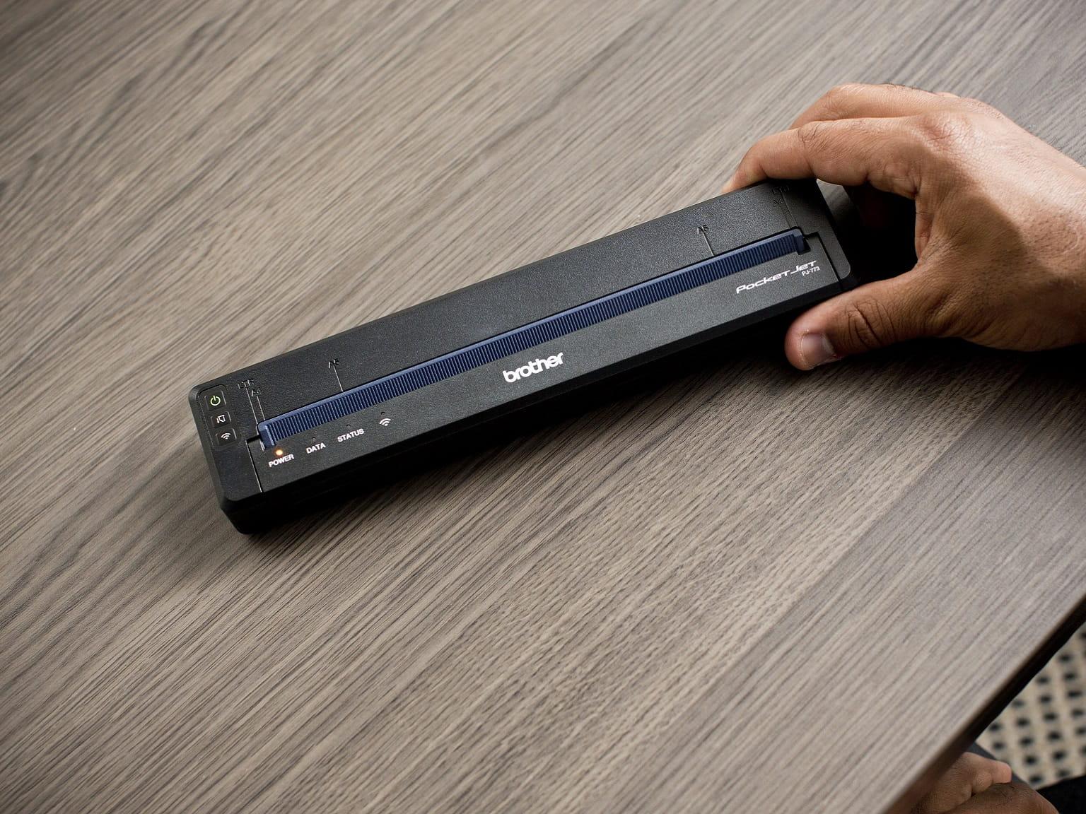 Stampante portatile Brother PJ-773 tenuta su scrivania in ufficio