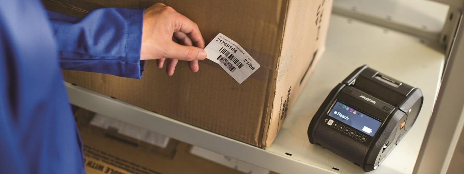 Lavoratore etichetta scatolone in magazzino con stampante Brother RJ3150