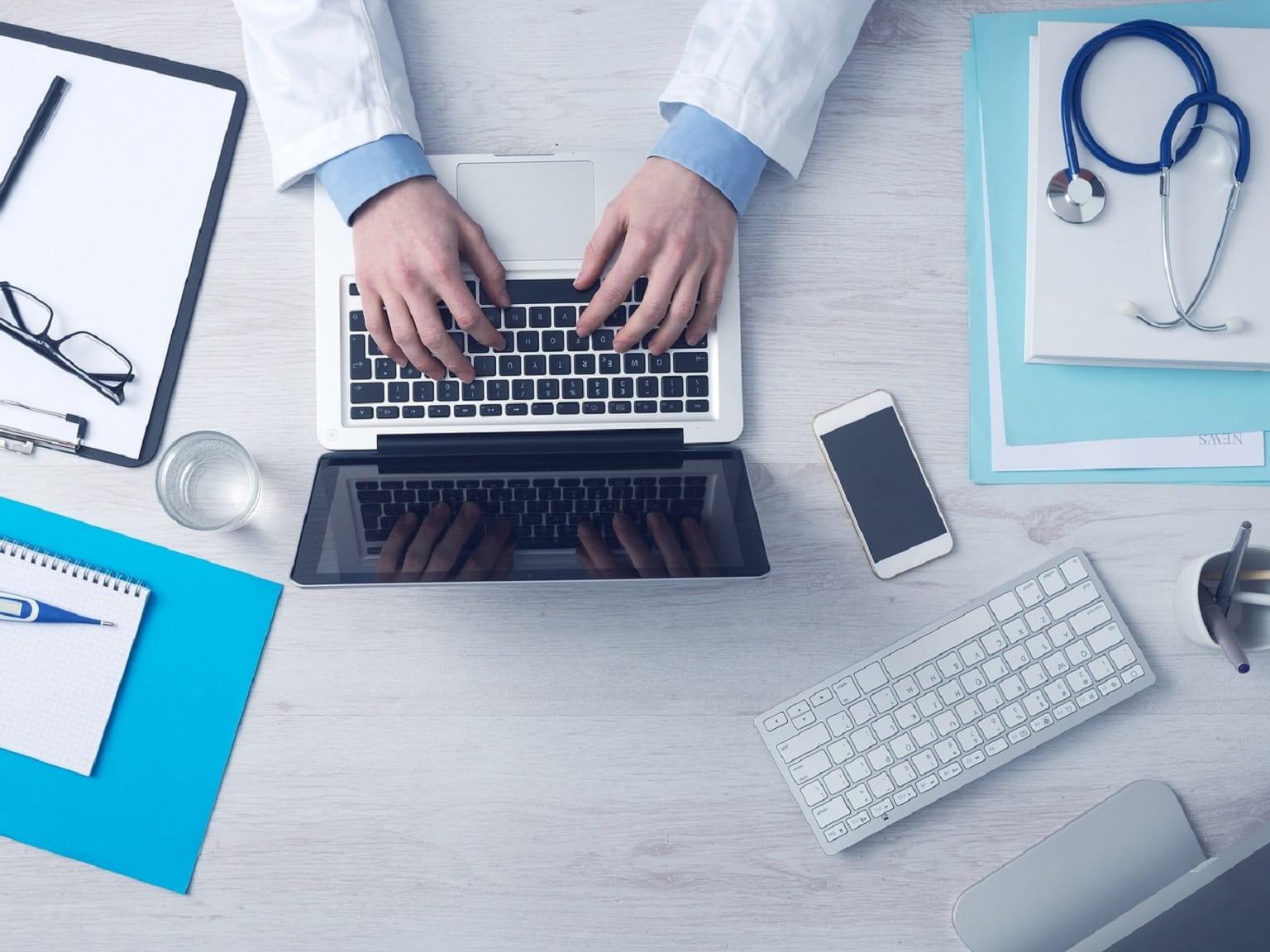 Medico al lavoro sul PC nel suo studio