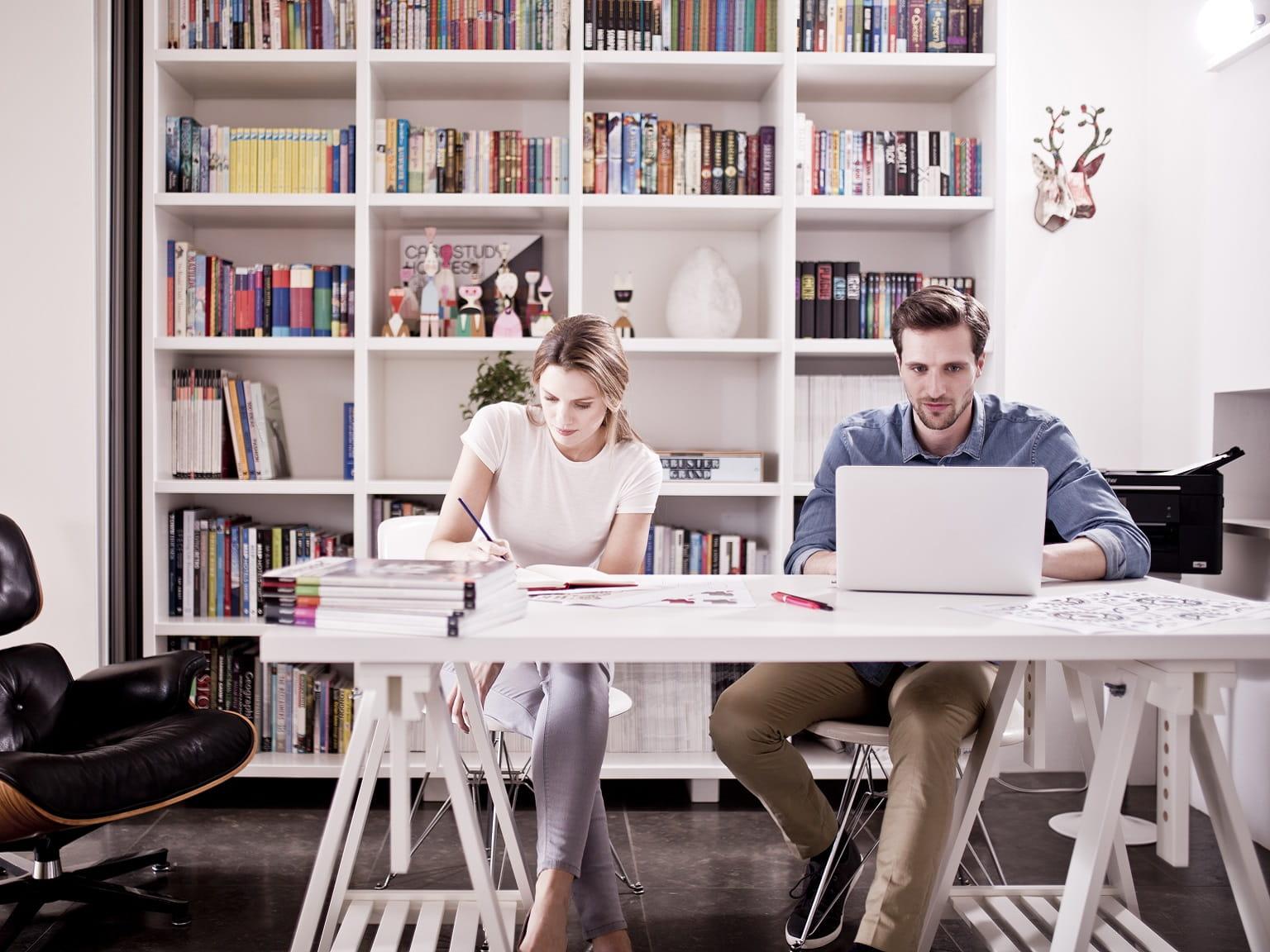 Colleghi al lavoro in ufficio SOHO con stampante multifunzione Brother