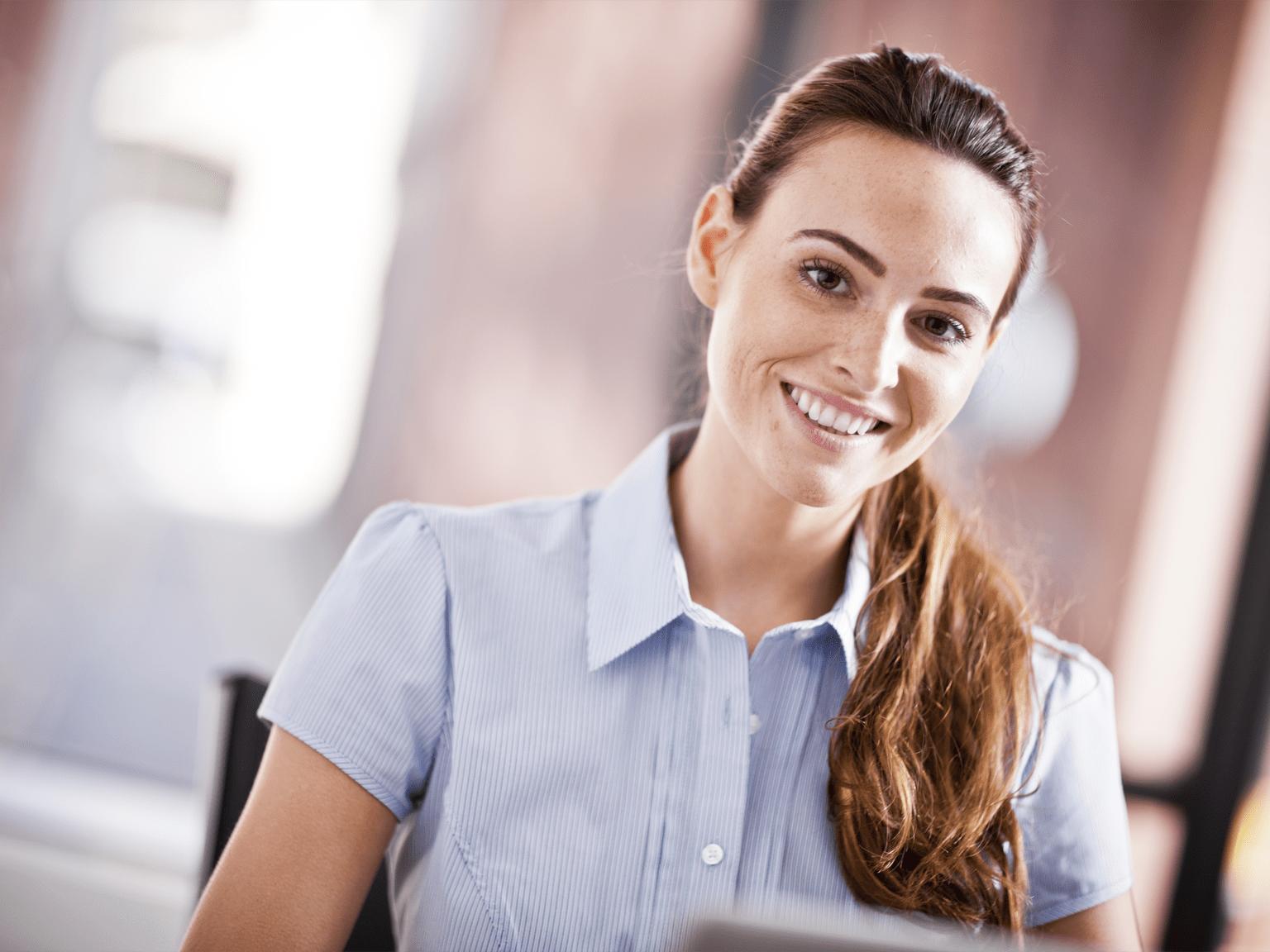 Impiegata sorridente al lavoro sul proprio PC portatile