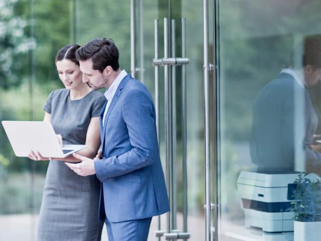 coppia di colleghi che guardano il pc davanti all'ingresso di un ufficio