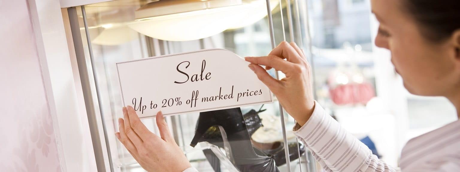 Impiegata attacca etichetta per sconti in negozio retail