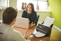 Impiegati in ufficio che scannerizzano documenti con scanner desktop Brother ADS-3000N