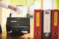 Scanner Brother ADS-2400N in azione con a fianco raccoglitori di documenti