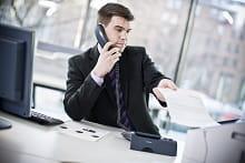 uomo utilizza fax nell'ufficio mentre telefona