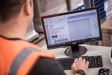 uomo utilizza computer desktop con stampante professionale di etichette