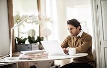 uomo utilizza portatile su tavolo con porta bianca