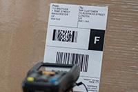 Scansione dell'etichetta con codice a barre sulla scatola marrone