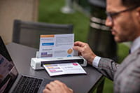 Uomo con laptop e  scanner portatile Brother DS740D scansiona documento A4 a colori