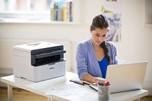 MFC-1910W girl browse internet with notebook and with a printer on the desk