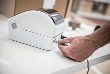 persona utilizza collegamento USB della stampante per etichette