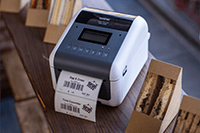Brother TD-4550DNWB desktop label printer printing food label next to sandwiches