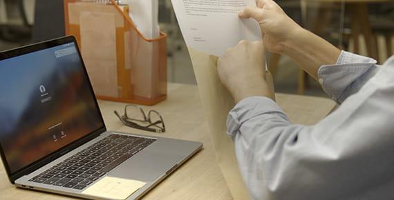 uomo seduto alla scrivania con pc che mette i documenti nella busta