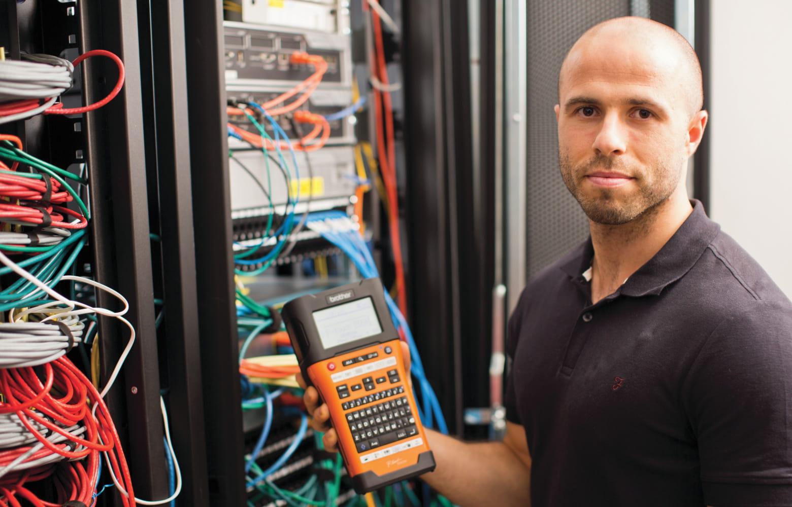Tecnico di rete tiene in mano una stampante di etichette P-touch