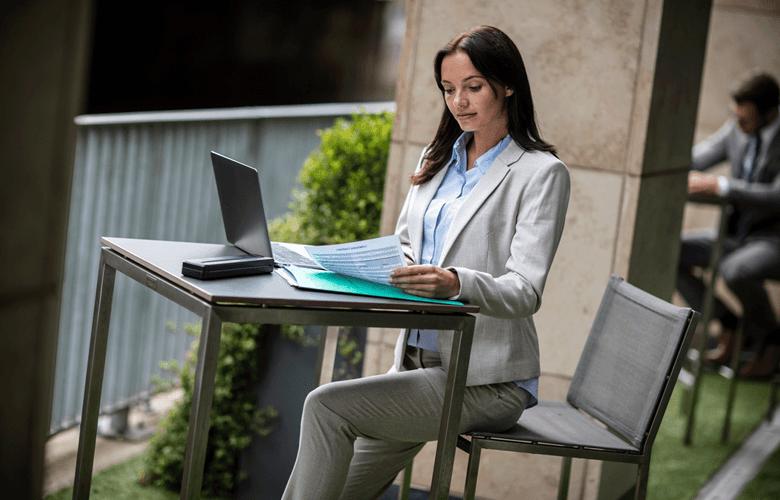 Donna seduta al tavolo pc laptop e stampante PJ