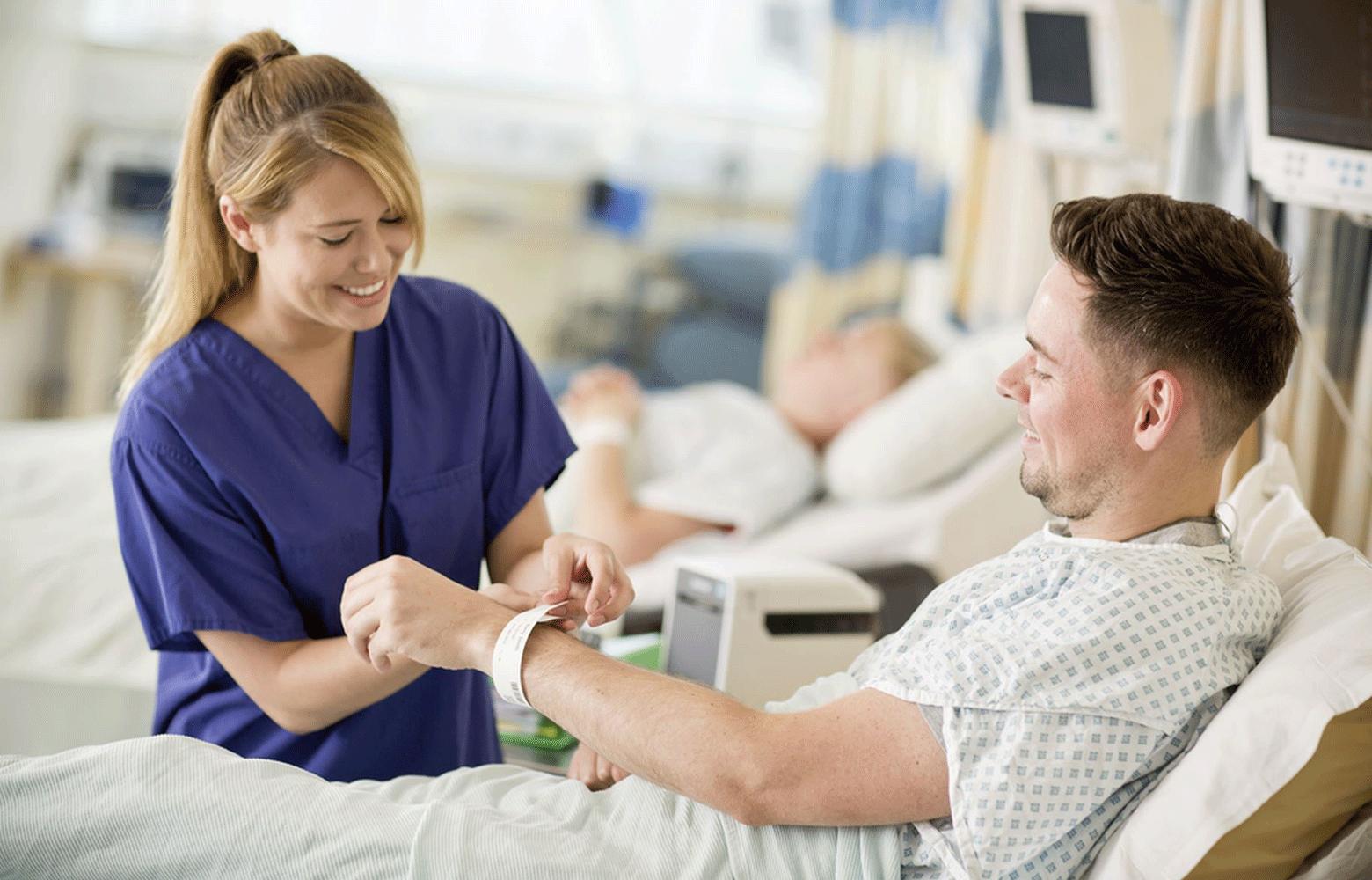 Infermiera mette il braccialetto al paziente maschio con stampante TD