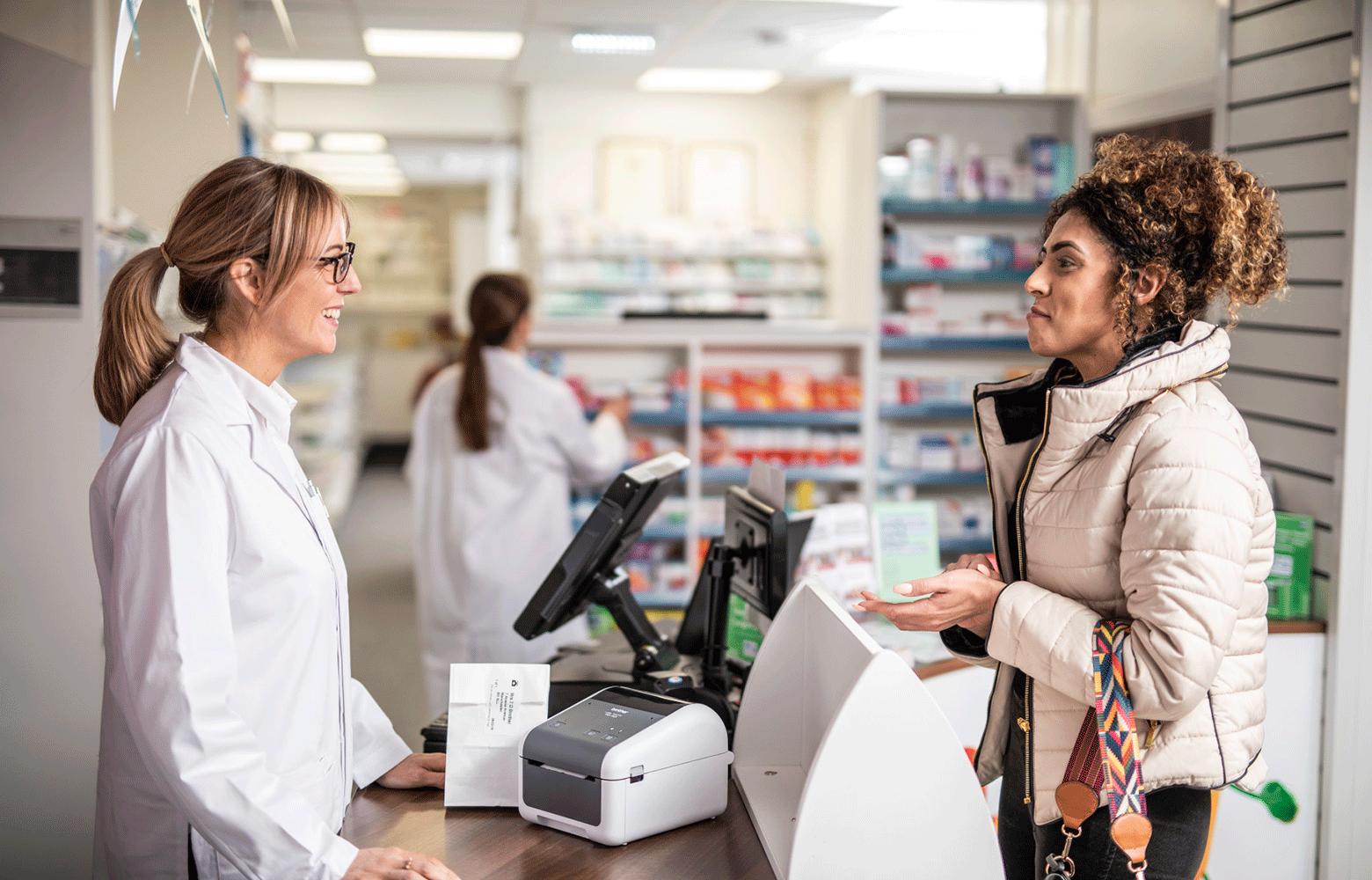 Farmacista parla con una cliente in farmacia. Stampante TD sul desk