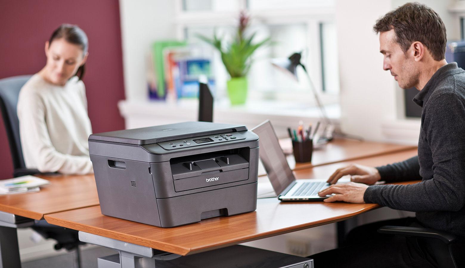 Impiegati al lavoro in ufficio con stampante multifunzione Brother DCP-L2520DW