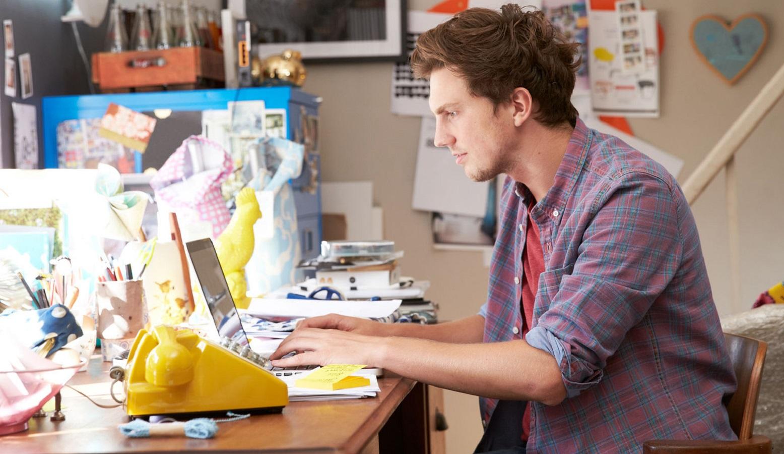 Giovane ragazzo al lavoro nel suo ufficio in casa