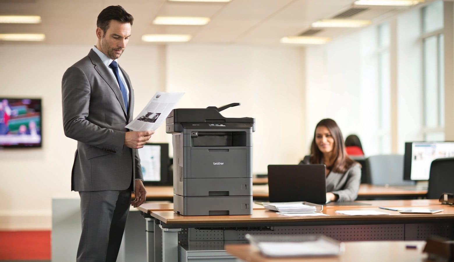 Impiegato in ufficio con foglio stampato dalla stampante multifunzione Brother MFCL5700DN