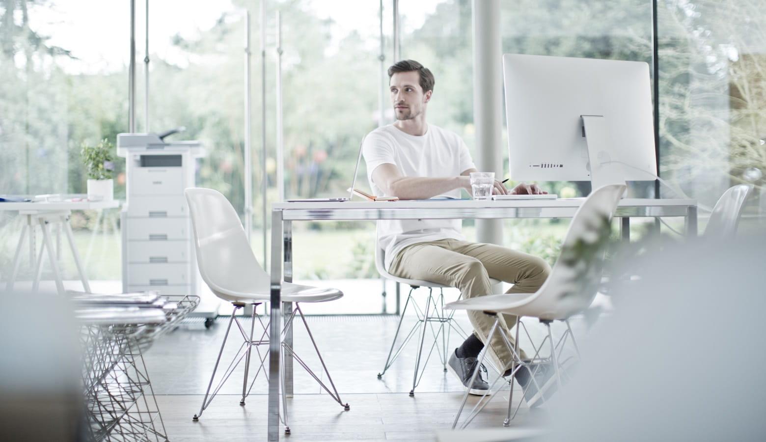 Ragazzo in ufficio open space con stampate multifunzione laser MFC-L6900DW